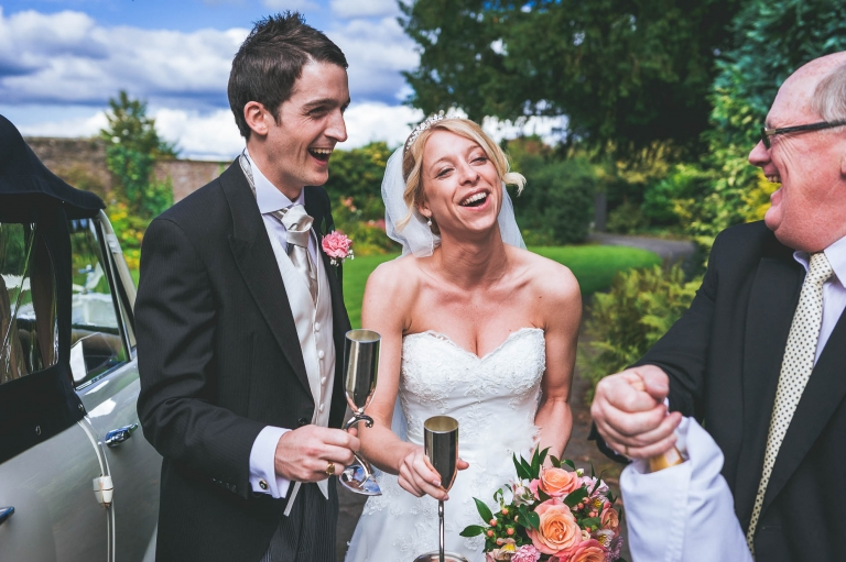 Bride and groom share a joke with chauffer