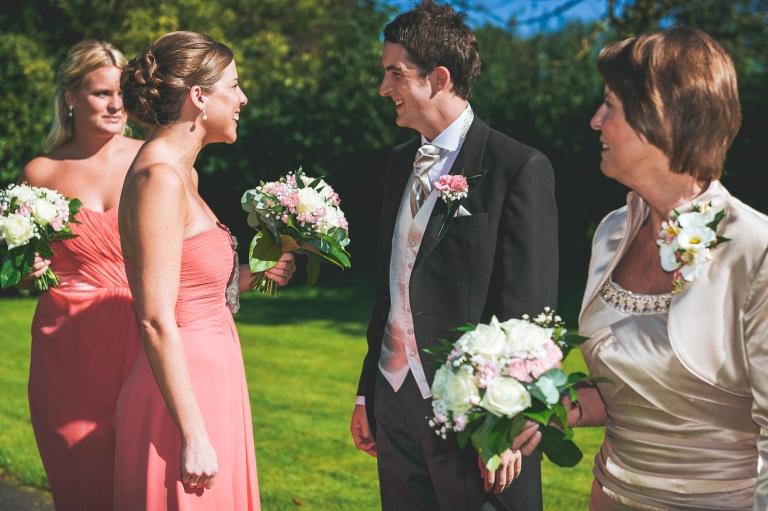 groom smiles at bridesmaid