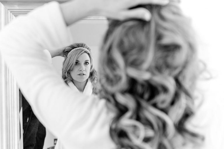 Bride adjusts her hair in mirror