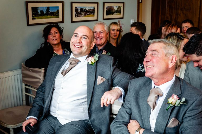Grooms brother sharing a joke with the groom