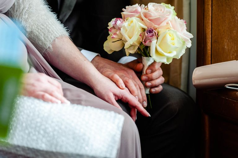 Bridesmaid holding hands with her partner