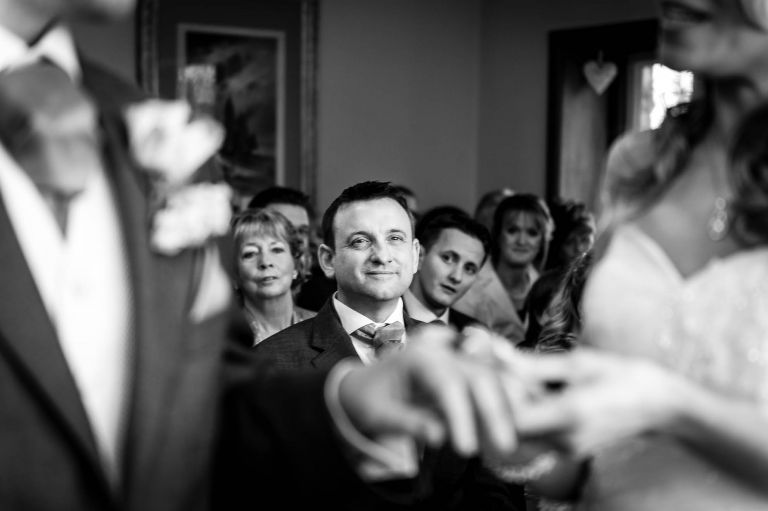 Brides brother smiles as he watches the ceremony