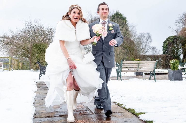 Bride and groom walk into marquee