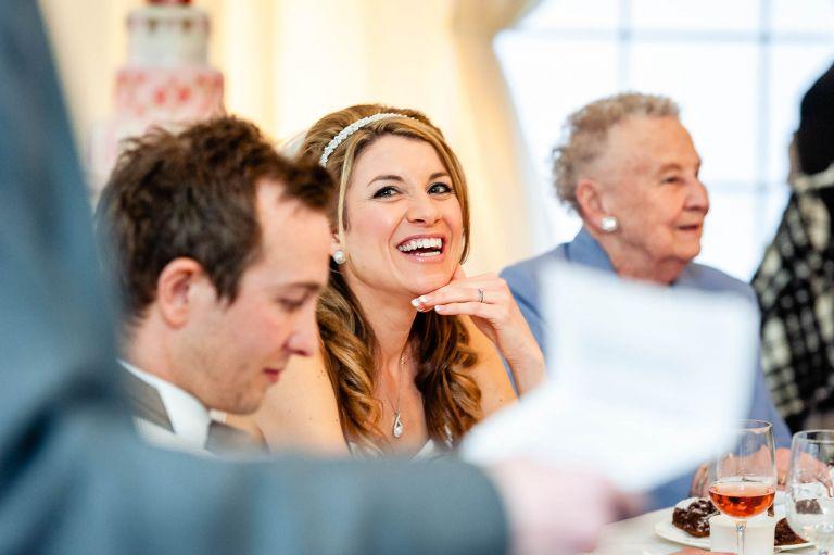 Bride smiles during best man's speech