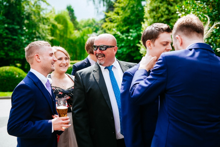 Wedding guest shares a joke with usher