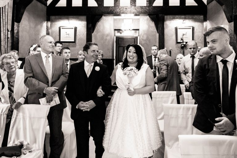 Bride smiles at groom as she walks up the aisle