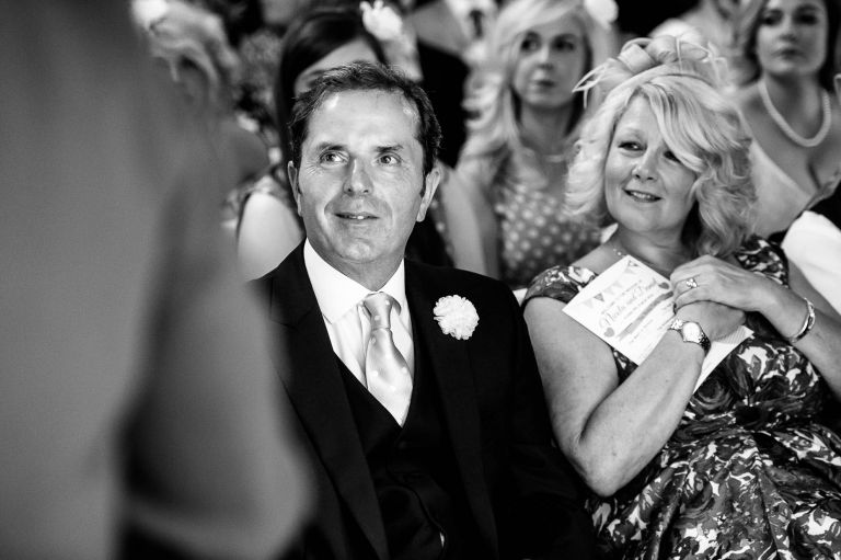 Father of the bride smiles as the newlyweds exchange rings