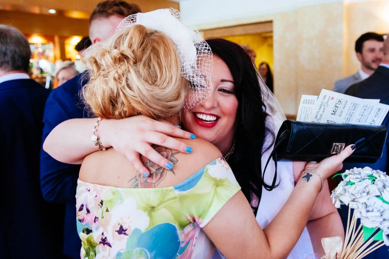 Bride gets a hug from a wedding guest