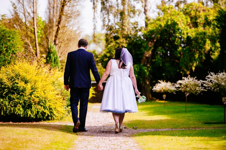 Bride and groom walk through gardens