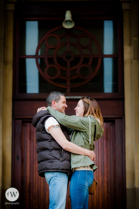 Couple holding each other in front of a door