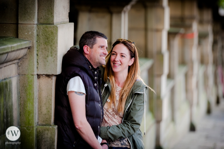 Couple sharing a joke leaning on wall