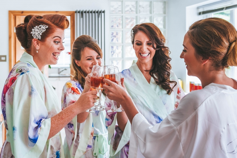 bridesmaid and bride drink champagne
