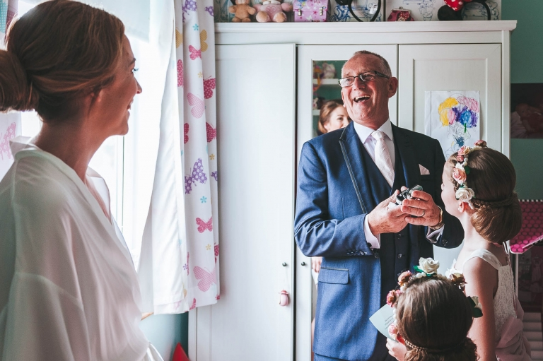 father of the bride laughs with bride