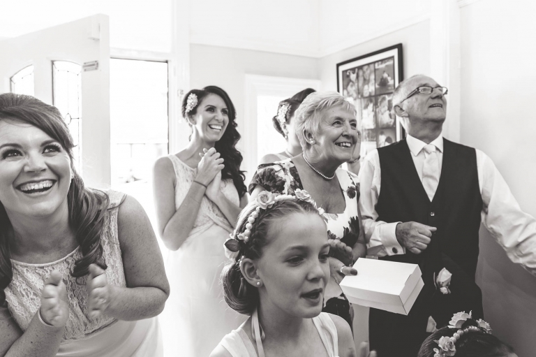 bridesmaids and brides mum and dad wait for bride to reveal her wedding dress