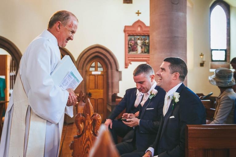 Groom shares a joke with priest