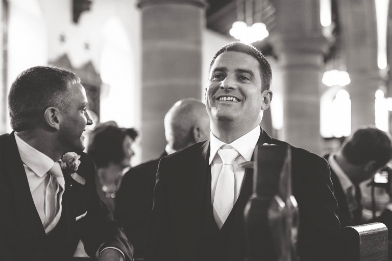 Groom smiles as he waits at the altar for his bride