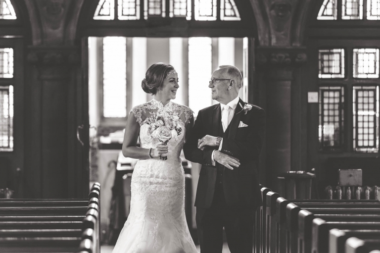 Father of the bride and the bride have a moment before they walk up the aisle