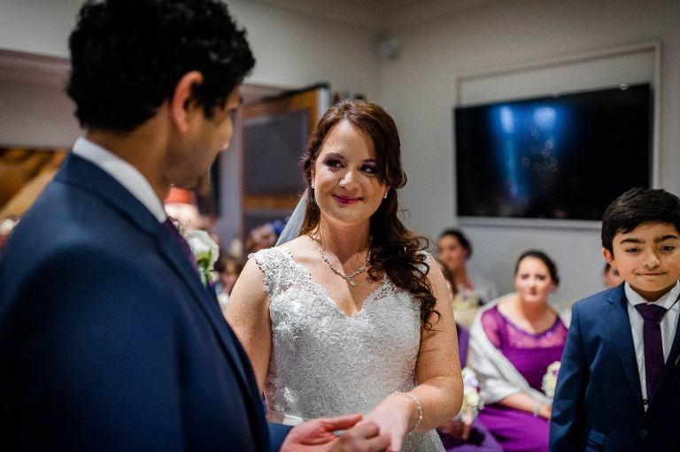 The bride smiles at the groom during the exchange of rings