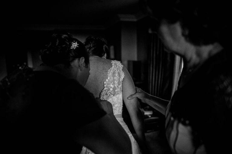 Bridesmaids help bride into dress