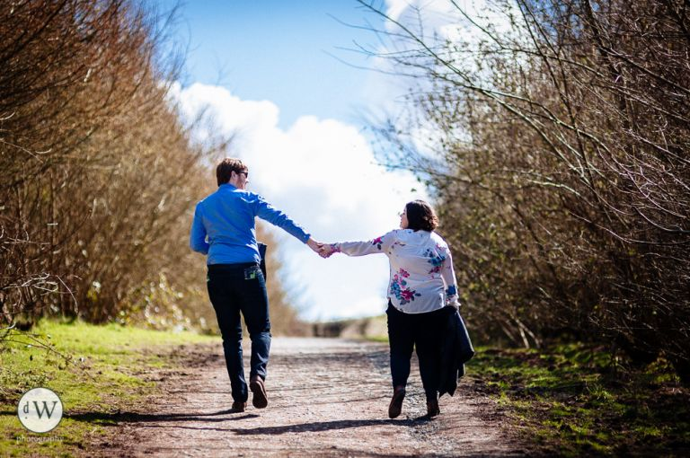 Engaged couple holding hands walking up hill