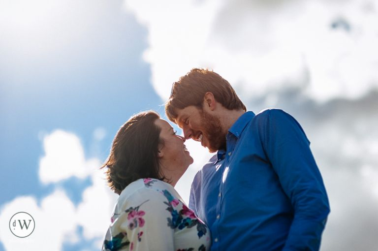 Couple kissing with sky background