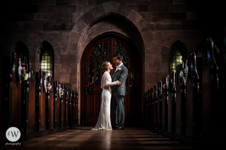 Bride and groom face each other by door of church