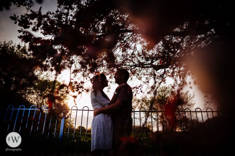 couple holding each other under a tree
