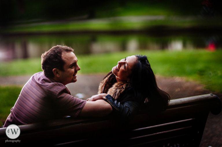 Couple sitting on bench share a joke
