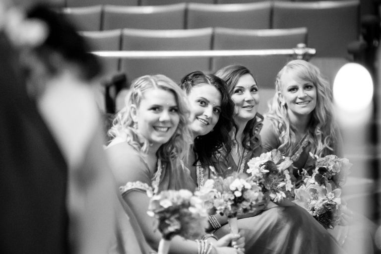 bridesmaids smile as they look at the bride and groom