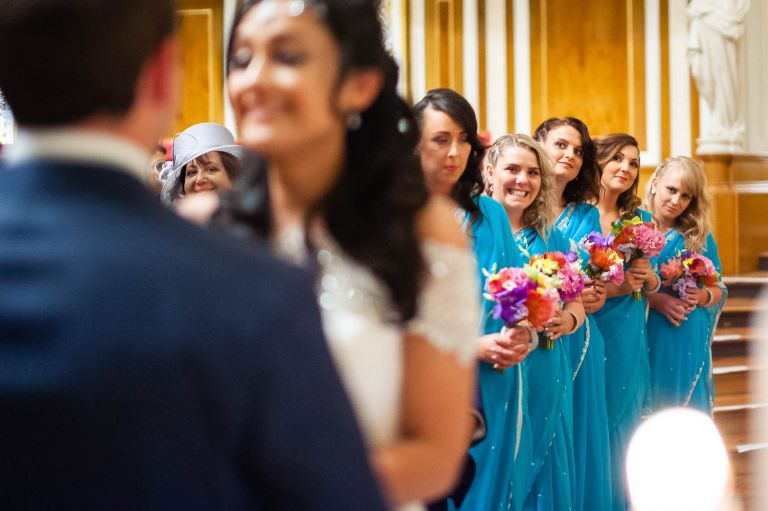 Bridesmaids smiling as they watch the exchange of rings