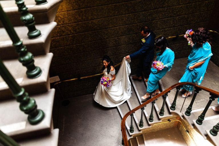 Bride walks down the stairs with groom and bridesmaids