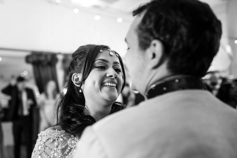 Bride smiles at the groom during the first dance