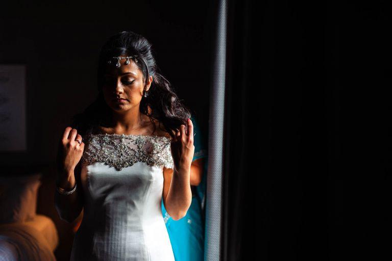 bride in wedding dress in window light