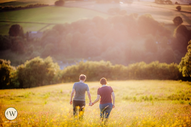 Couple walking holding hands in a meadow