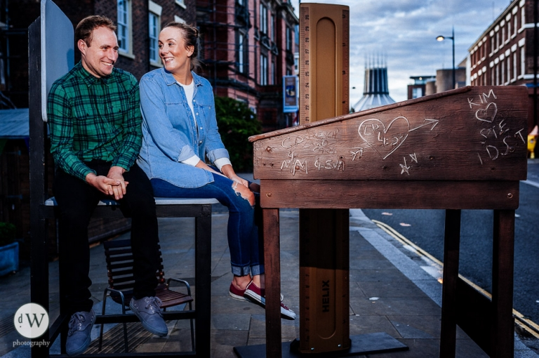 Couple sitting at a giant school desk