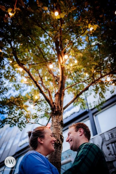 Couple share a joke under a tree