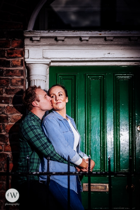 Man kissing woman in front of a door
