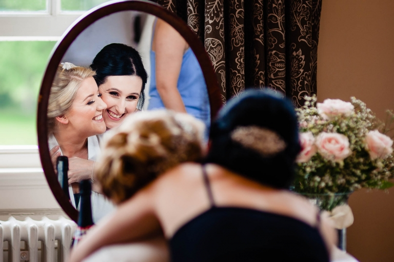 Bride gets a hug from a bridesmaid during the bridal preparations