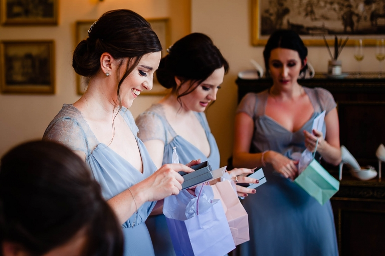 Bridesmaid smiling as she opens her present