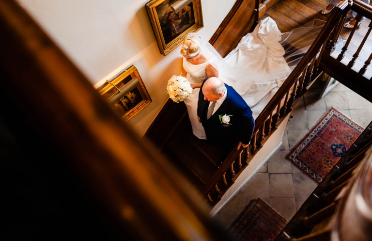 Bride walks down stairs with father towards wedding ceremony