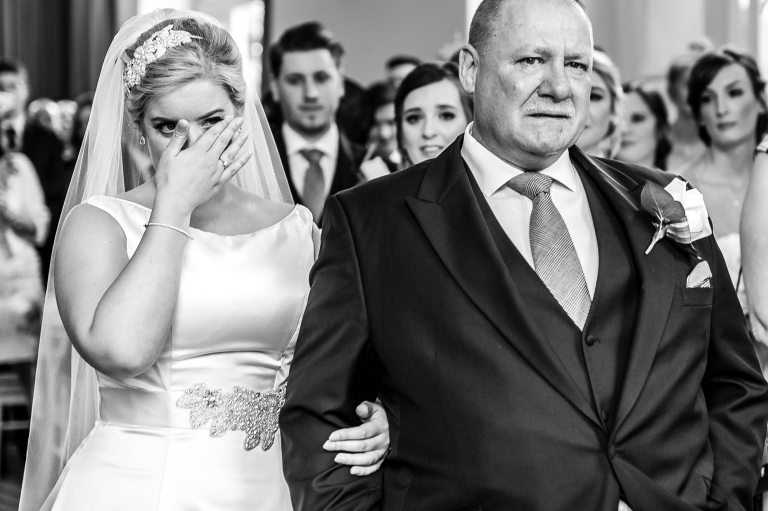 Bride wipes away a tear as she arrives at the ceremony