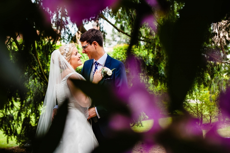 Bride and groom portrait surrounded by flowers