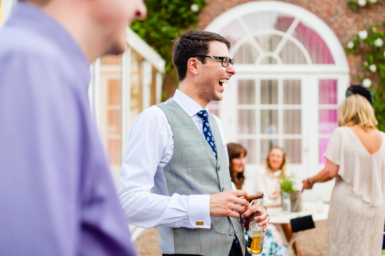 Groom shares a joke with a guest