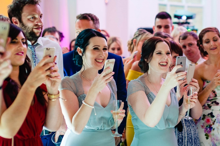 Bridesmaids smile as they watch the first dance