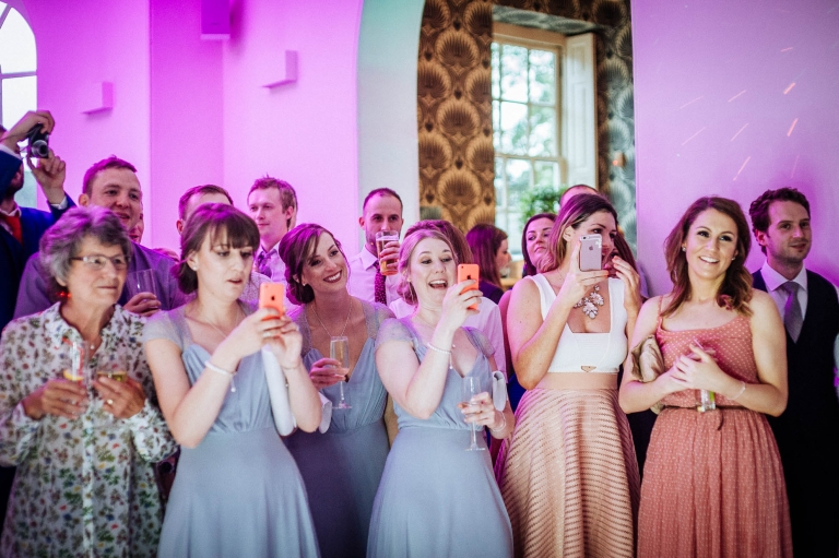 Bridesmaids taking photographs of the first dance