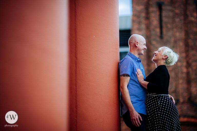 Couple leaning against pillar