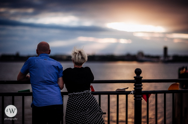 Couple looking out over the Mersey sunset