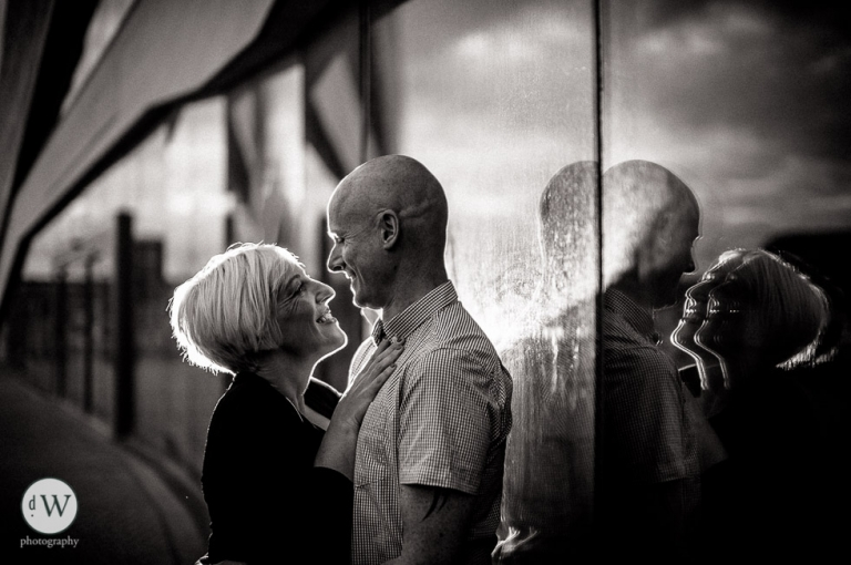 Couple holding each other with reflection in galss