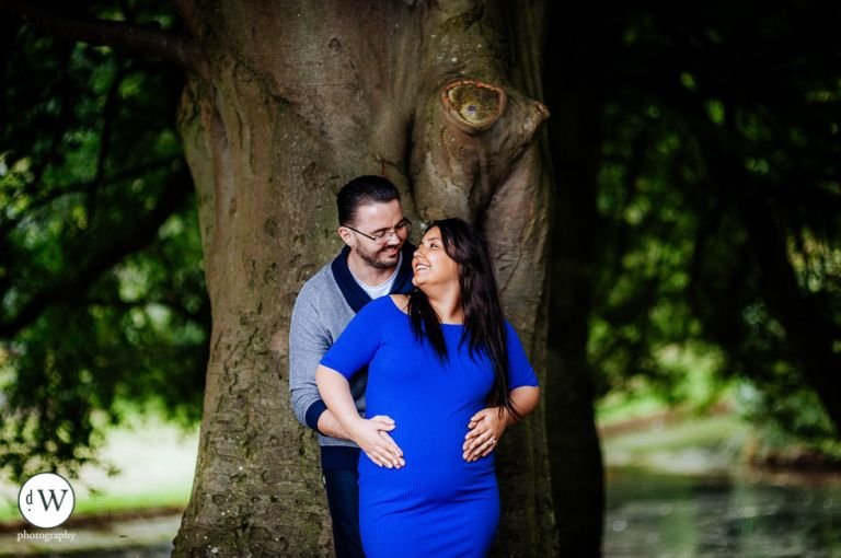 Couple holding each other by a tree