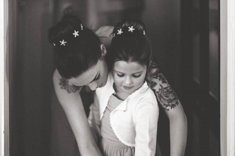 Bridesmaid helps flower girl get ready